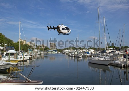 Helicopter bringing boat owner to his yacht dockside on ocean front