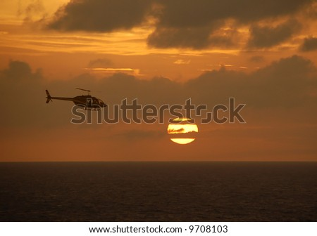 Helicopter by sunset - stock photo