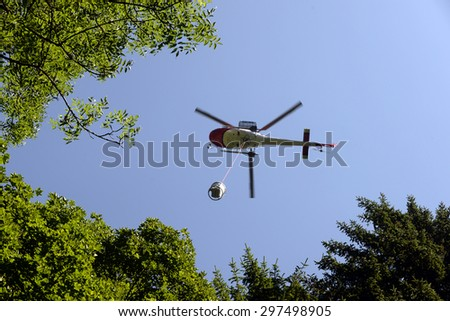 helicopter carries cargo in the Alps at a construction site - stock photo