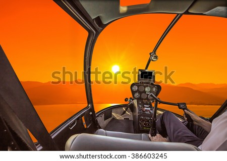 Helicopter cockpit on the sea at sunset, with pilot arm and control board inside the cabin - stock photo