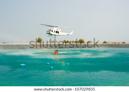 Helicopter dipping its bucket to load water - stock photo