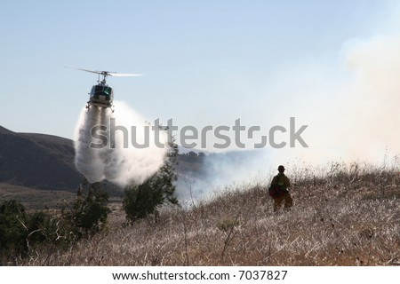 Helicopter drops water on a brush fire as a firefighter watches on - stock photo