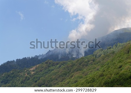 Helicopter fighting wide spread mountain forest fire - stock photo