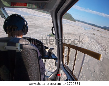 Helicopter flight over a rugged wilderness landscape in new zealand, seen from the cockpit - stock photo