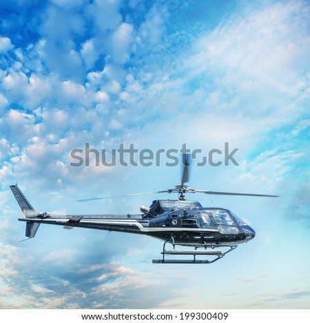 Helicopter flying against the blue sky. - stock photo
