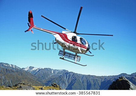 helicopter flying in mountains