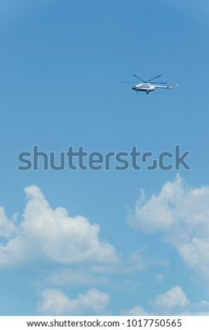 helicopter flying in the blue sky with clouds