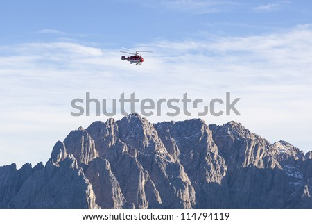 Helicopter flying over the mountains - stock photo