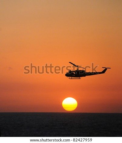 Helicopter flying over the seat sunset