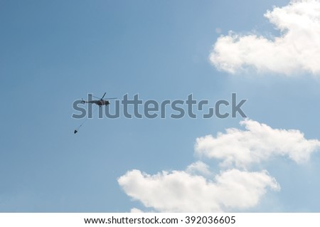 Helicopter in action carrying water bucket - stock photo
