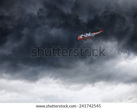 Helicopter in Norway seen from below in front dramatic sky.  - stock photo