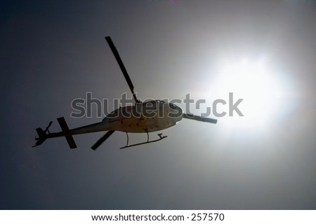 Helicopter in the air over gray background. - stock photo
