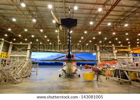 helicopter in the hangar is prepared for morning flight - stock photo