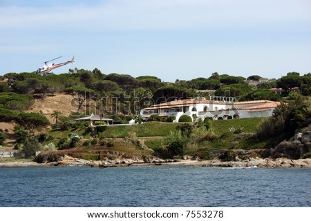 Helicopter is flying away from a luxury residence among old trees on a coast of Saint Tropez, French riviera