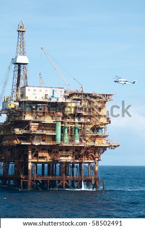 Helicopter landing in offshore oil rig.  Coast of Brazil - stock photo