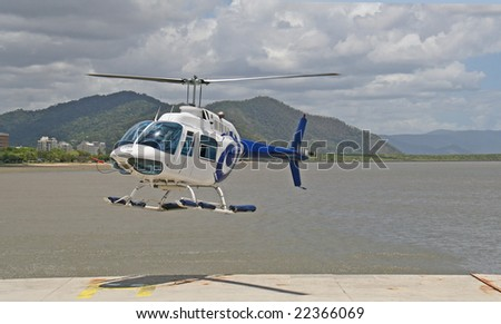 helicopter landing on pontoon with sea in background. room fro text.