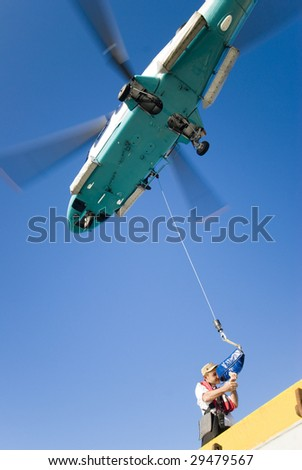 helicopter operation (person preparing for hoisting operation) - stock photo