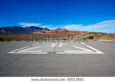 Helicopter pad against the dry landscape and red rock formations of the Mojave Desert. - stock photo