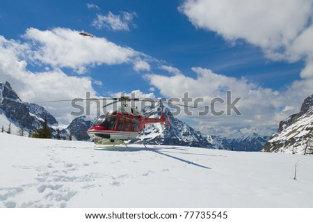 Helicopter parked on a mountain peak during a tour of Marvel pass on the boarder of Britsh Columbia and Alberta - stock photo