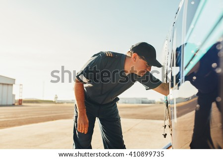 Helicopter pilot checking the engine condition of helicopter before take off. Pilot doing pre flight inspection. - stock photo