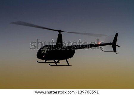 Helicopter silhouette in flight at sunset
