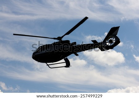 helicopter silhouette in the blue sky - stock photo