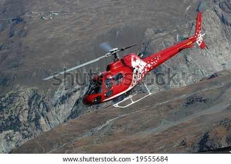 Helicopter supplying the mountain huts in the mountains around Zermatt, Switzerland. In the background can be seen the Gornergerat - stock photo