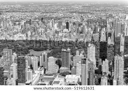 Helicopter view of Central Park and city skyscrapers in Manhattan on a sunny day.