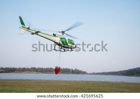 Helicopter with a Bambi bucket filled to fight a forest fire - stock photo