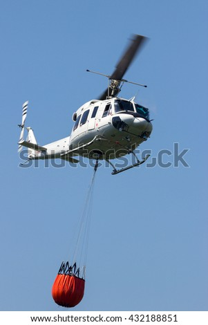 Helicopter with a Bambi bucket filled with water to fight a forest fire - stock photo