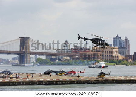 Helicopters leaving for sight-seeing tours above New York City, U.S.A., Downtown Manhattan Heliport, August 4th 2014, 1:09 p.m. - stock photo