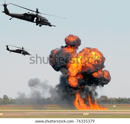 Helicopters mounting a ground attack with explosions and smoke - stock photo