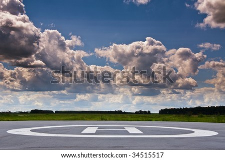 Helipad in the field in cloudy day. - stock photo