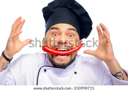 Hell kitchen. Closeup portrait of emotional handsome funny cook holding red pepper in his mouth while standing over white background with copy space - stock photo