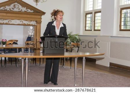 HELLEVOETSLUIS,HOLLAND-JUNE 13,2015:Woman speaking to public behind the desk in the city hall on June 13, Hellevoetsluis,the city hall is a very old room used for weddings