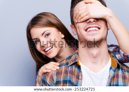 Hello! Beautiful young women covering eyes of her boyfriend and peeking out his back while standing against grey background  - stock photo