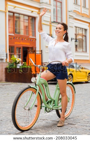 Hello! Full length of attractive young smiling woman waving to someone while riding her vintage bicycle along the street - stock photo