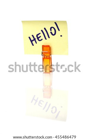 Hello  message written on a yellow paper note with a clothespins holding isolated on white background with reflections. - stock photo