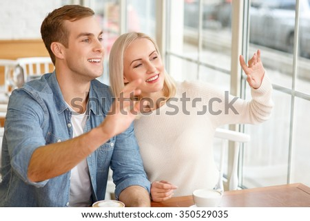 Hello. Pleasant smiling jubilant couple sitting at the table in the cafe and drinking coffee while welcoming someone