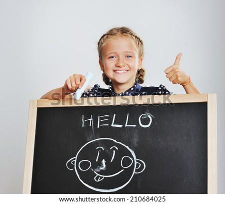 Hello school girl drawing on blackboard - stock photo