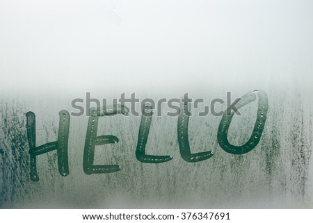 Hello world sigh written on fogged window, closeup. Foggy texture background copy space close up - stock photo