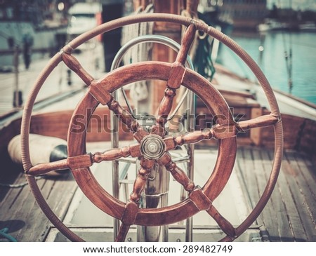 Helm on a vintage wooden yacht  - stock photo
