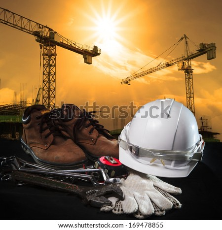 helmet and construction equipment with building and crane against dusky sky use for construction business theme - stock photo