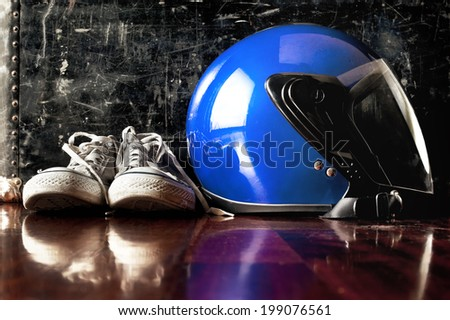 Helmet and dirty sneakers on floor in front of vintage suitcase - stock photo