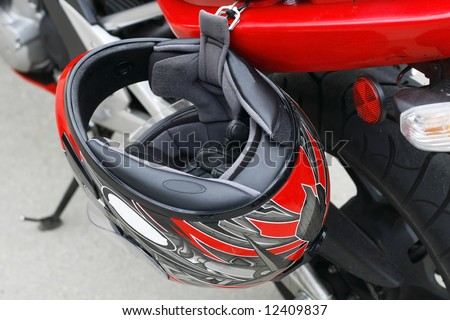 helmet and gloves hanging from parked motorcycle