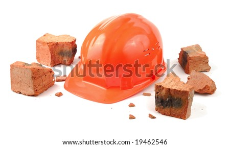 Helmet and pieces of broken brick isolated over white - stock photo