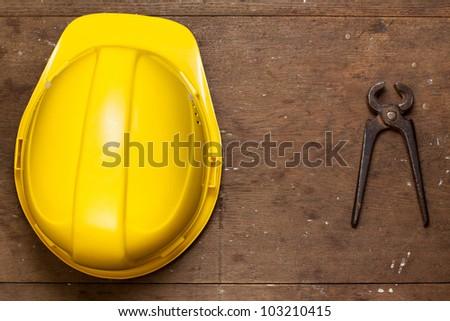 Helmet and pincers on grunge oak wood - stock photo