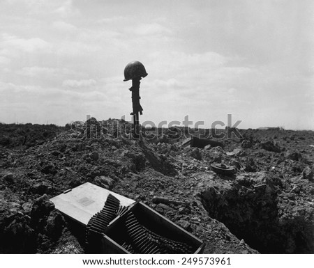 Helmet and rifle monument to a dead U.S. soldier on a shell-blasted beach of France. He was killed on D-Day during the Normandy landings, June 6, 1944, World War 2. - stock photo