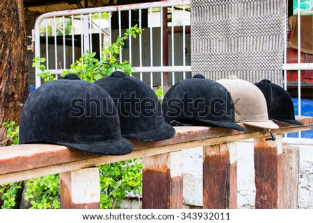 Helmets jockeys lying on a wooden stand near the site for training - stock photo