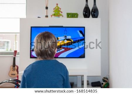 HELMOND, NETHERLANDS - JULY 24, 2012: Little unidentified child watching a cartoon on a HD flat screen TV in a modern living room. - stock photo